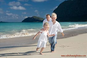 Father with children running on the beach at Waimanalo Beach Oahu Hawaii
