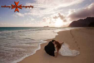 Bride and Groom sitting and kissing on the sand Waimanalo Oahu Hawaii