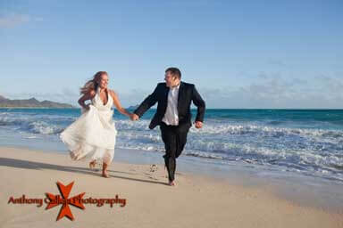 Bride and Groom smiling, holding hands, and running on the beach Waimanalo Oahu Hawaii
