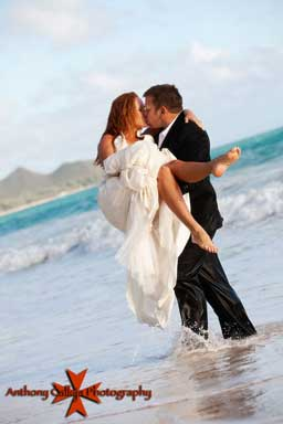 Groom carrying and kissing Bride in the waters of Waimanalo Beach Oahu Hawaii