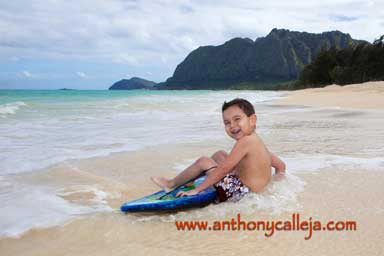 little boy having fun boogie bording on the beach at Waimanalo Beach Oahu Hawaii