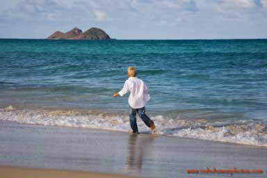 young boy running on the white sand beach of Waimanalo Beach Oahu Hawaii