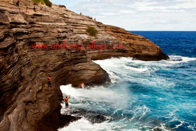 Cliff Jumper dives in the waters at Spitting Cave of Portlock