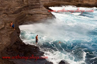 Cliff Jumpers observe the spay at Spitting Cave of Portlock, Oahu, Hawaii