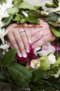 Hawaii Wedding Rings photo of Bride and Grooms hands wearing wedding rings with flower bouquet and flower lei