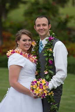 Bride and Groom holding flowers in a garden at laie Temple