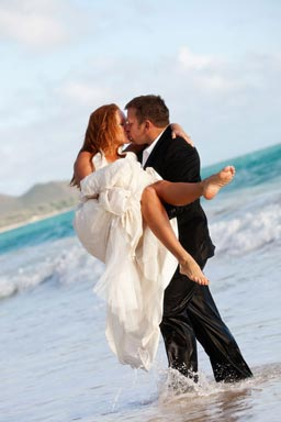 Groom carrying bride in the water kissing
