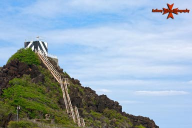The Pyramid Rock Light currently consists of a light mounted on the roof of a square concrete workhouse, painted with distinctive black & white diagonal stripes. The light guides vessels into Kaneohe Bay & overlooks a recreational beach for the marines.