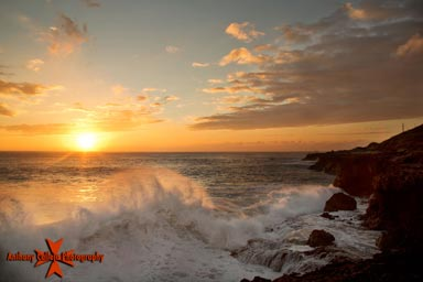 Sunset and crashing waves Kaena point, Oahu Island